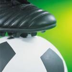 La scarpetta di un calciatore sul pallone (particolare)