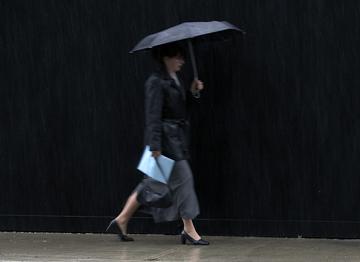 Donna con ombrello sotto una fitta pioggia